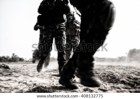 The troops move forward with movement and dark tone. - stock photo