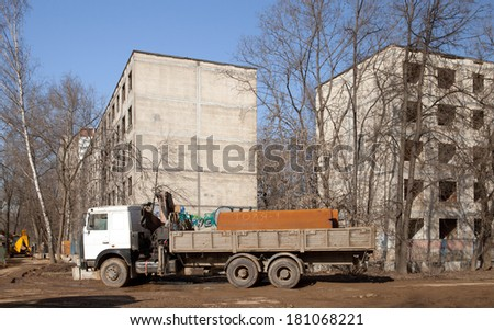 The truck with big tube on demolition of 5 levels buildings - stock photo