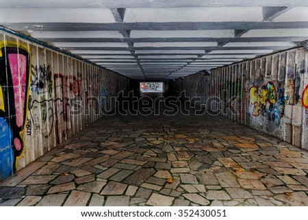 The tunnel underground pedestrian crossing with pictures of graffiti on the walls. The original light-shadow gradation. Ideal for the creative design of stage. Selective focus. - stock photo