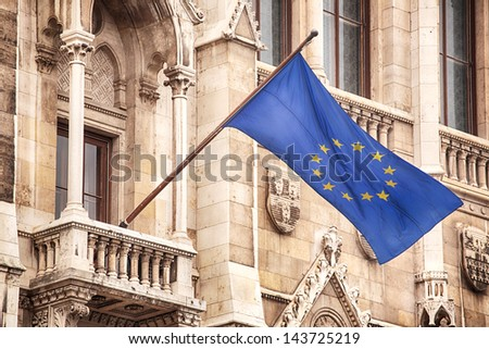 The twelve yellow star flag of Europe (also known as Flag of the European Union and of the Council of Europe) waving from the facade of an old building. - stock photo