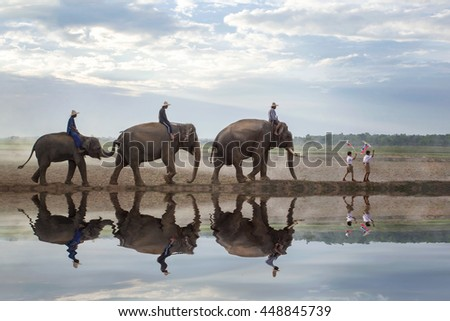 The two boys went before the parade elephants. Two children waving flags in their hands.  at the surface of the water with the reflection of everything. - stock photo