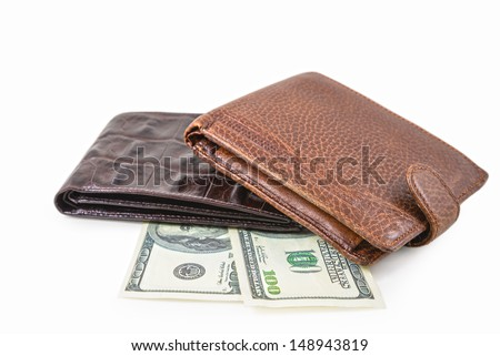The two brown  leather wallet with dollars is photographed on the close-up