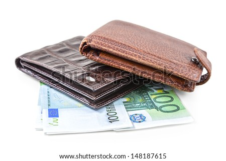 The two brown  leather wallet with euro and dollars is photographed on the close-up