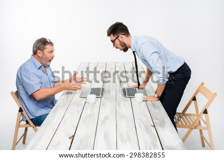 The two colleagues working together at office on light gray background. Both are looking at the computer screens and  surprising.  the concept of competition in the business       - stock photo