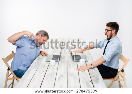 The two colleagues working together at office on white  background. both are looking at the computer screens. both furiously shouting. concept of negative emotions and bad news