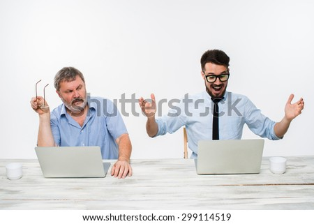 The two colleagues working together at office on white  background. both men are looking at the computer screens. a young man getting good news. the old man is upset. concept of competition in - stock photo