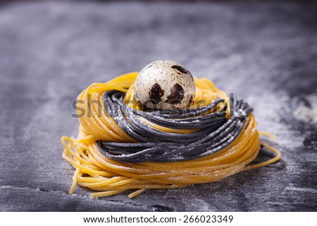 The two-color pasta homemade raw materials in the form of nests with quail egg, on a dark background.Easter decorations, selective focus. - stock photo