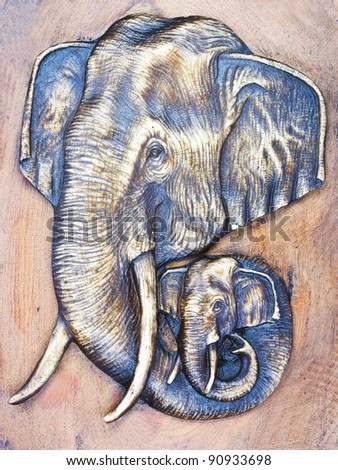 The two elephants  head on a piece of wood. - stock photo