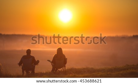 The two people sit against the background of sunset - stock photo