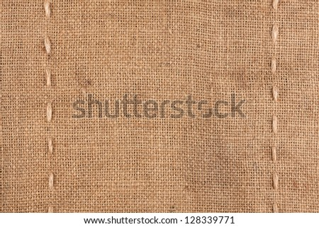 The two vertical stitching on the burlap as background - stock photo