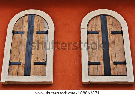 the two windows made from wood on the red wall - stock photo