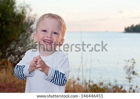 the two-year-old kid laughs against the sea - stock photo