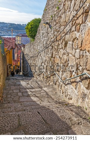 The typical narrow and steep medieval street of the older parts of the city, connecting the Cathedral zone to the Ribeira District.  of Porto, Portugal. Unesco World Heritage Site - stock photo