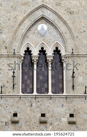 The typical three-part Sienese gothic windows of Palazzo Salimbeni, the 14th century headquarters of the world's oldest bank: Monte dei Paschi di Siena. Siena, Italy. - stock photo