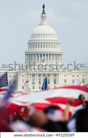 The U.S. Capitol building in the distance, American flags fly on the National Mall during a political rally. - stock photo