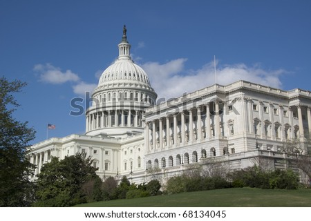 The U.S. Capitol Building on a Bright Spring Day Against a Bright Blue Sky With a Few Puffy White Clouds - stock photo