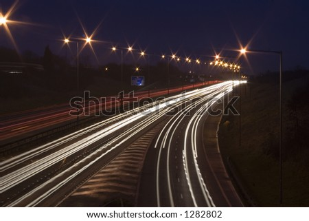 The UK's largest freeway at night. Cars speeding fast creating light trail and blurs on motorway. - stock photo