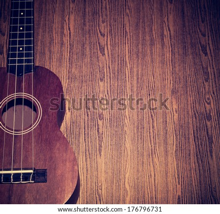 The ukulele is placed on a vintage wooden floor. - stock photo
