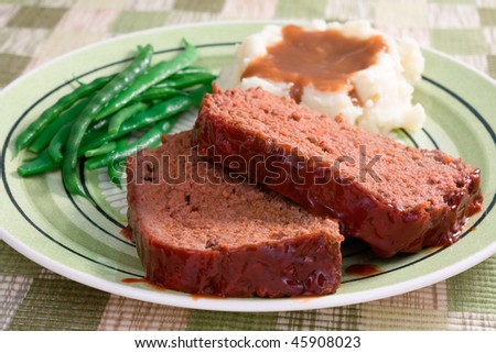 The ultimate comfort food - meat loaf prepared with ground beef, grated carrots, bread crumbs, and herbs and spices. Served with fresh green beans, mashed potatoes, and gravy. - stock photo