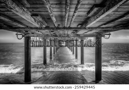 The underside of a pier with rest area on the end of it, black and white - stock photo