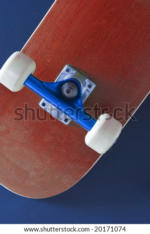 the underside of a red colored skateboard on a blue background