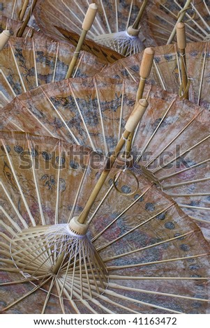 The underside of handmade oiled rice paper umbrellas at the Umbrella Making Centre in Bo Sang, Thailand. - stock photo
