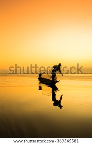 The unfocused silhouette of a fishing boat with Myanmar. - stock photo