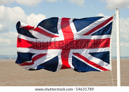 The Union Jack British flag rippled on a windy day at sea - stock photo