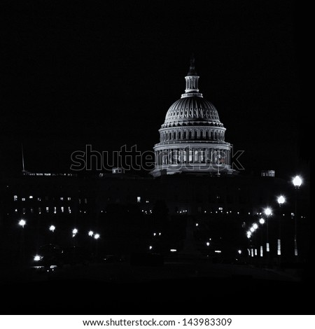 The United States Capitol building lit up at night, Washington D.C., USA in black and white with American flag in color.  This landmark building is a symbol of liberty and freedom for many.