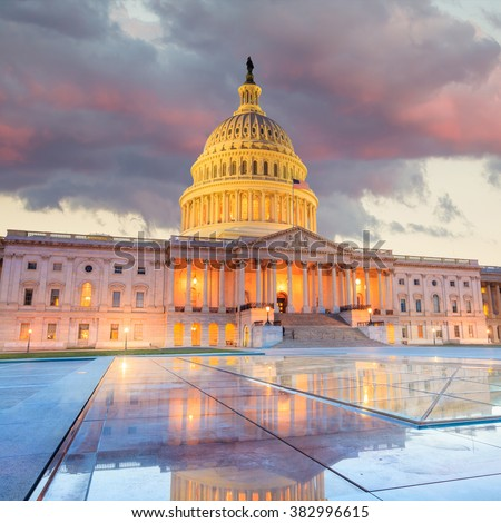 The United States Capitol building with the dome lit up at night.  - stock photo