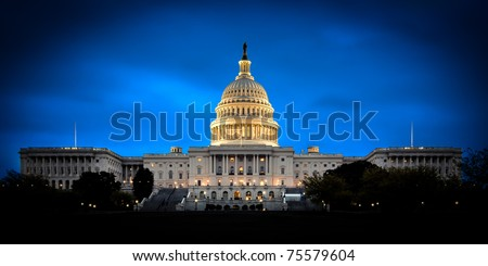 The United States Capitol building with the dome lit up at night.  Both the Senate and House sides of the building are fully shown. - stock photo