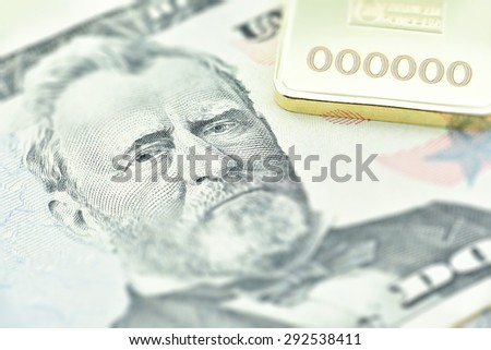 The United States fifty dollar bill, a macro close-up with gold bullion - stock photo