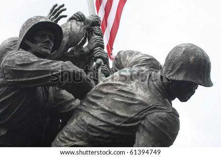 The United States Marine Corps War Memorial in a close-up of the Marines raising the American Flag.  Stark, with the flag lending color to the scene. - stock photo