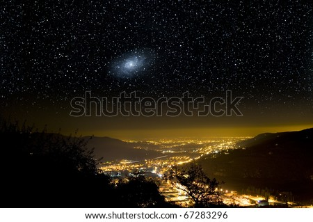 The Universe above city lights. The Triangulum galaxy, M33. - stock photo