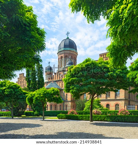 The university church is hidden behind the scenic shady garden, Chernivtsi, Ukraine.