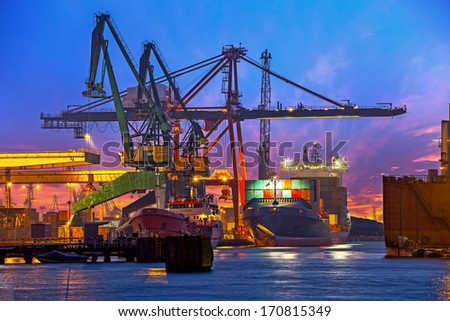 The unloading of a container ship at a large harbor terminal. - stock photo
