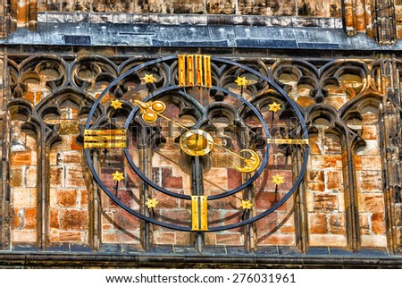 the unusual clock of the cathedral of St Vitus in Prague, a church with dark Gothic towers guarded by gargoyle: this church is the main religious symbol of the Czech Republic - stock photo