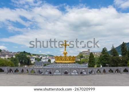 The Upper Basilica with gilded crown ad cross in Lourdes - stock photo