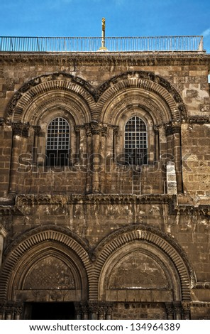 The upper part of the entrance to the Church of the Holy Sepulchre in the old city of Jerusalem. Just below the right window, the famous ladder of the status quo is seen (it's been there since 1854). - stock photo
