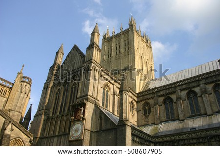 The upper part of the north side of Wells Cathedral, Somerset showing the medieval clock. Background of blue sky with white clouds.