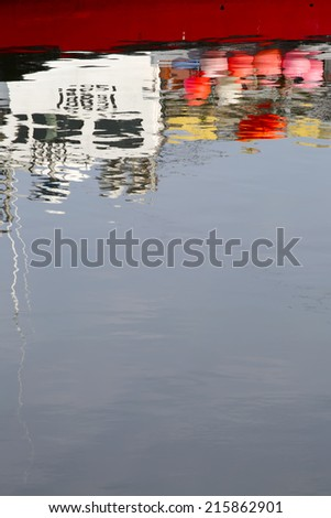 The upside down refleciton of a fishing boat in the harbour. - stock photo