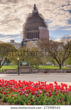 The US Capitol dome in Washington, DC is covered with scaffolding as it undergoes a facelift to restore cracks in the cast iron architecture. - stock photo