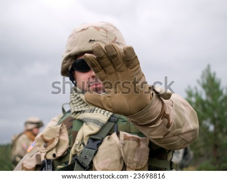 The US Soldier showing arm to stop some action (for example, filming or walking, etc.) - stock photo