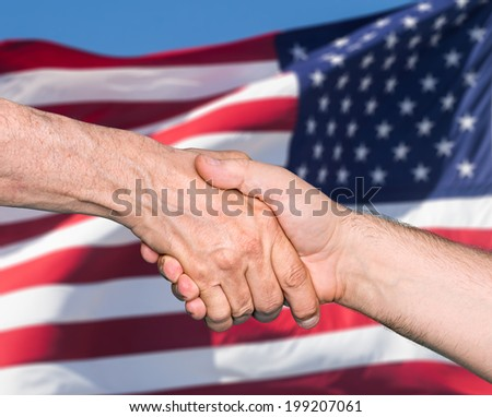 The USA flag and shaking hands of two male people - stock photo