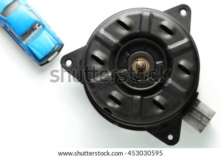 The used and damaged old fan motor unit with model toy car put beside represent the car part and maintenance concept related idea.
