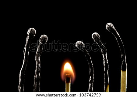 The used matches on a black background (one match burns). - stock photo