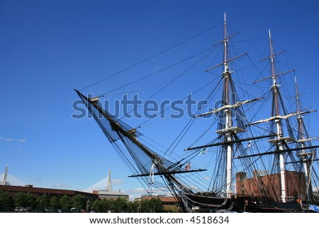 The USS Constitution in Boston, Massachusetts.  Zakim Bunker Hill Bridge in the background. - stock photo