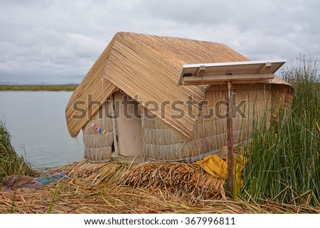 The utilization of solar power to gather alternative energy power from the sun to generate electricity in the rural reed houses of the Uros island on Lake Titicaca, Puno, Peru.  - stock photo