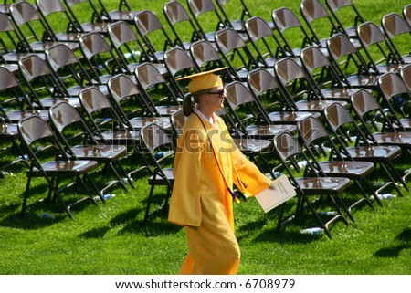 The valedictorian for her graduating class marches to her place at the head of the class. - stock photo