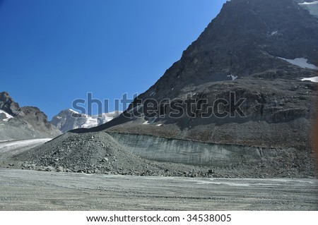 the valley of a retreating glacier.  A wall of ice shows where the glacier level has been in recent times. Global warming is causing glaciers to melt and sea levels to rise - stock photo